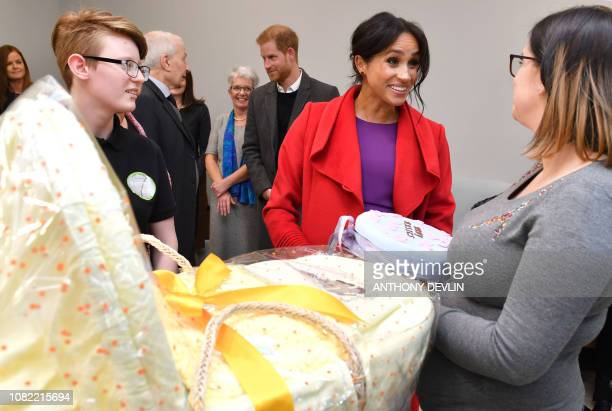Meghan Duchess of Sussex presents Angela Midgley with a baby's moses basket as she officially opens 'Number 7' a 'Feeding Birkenhead' citizens'...