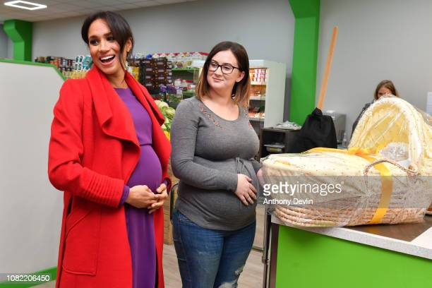 Meghan Duchess of Sussex presents Angela Midgley with a Moses basket at 'Number Seven' a 'Feeding Birkenhead' citizen's supermarket and community...