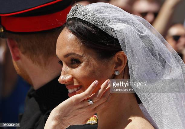 Meghan Duchess of Sussex reacts from the Ascot Landau Carriage during the carriage procession with Britain's Prince Harry Duke of Sussex on the High...