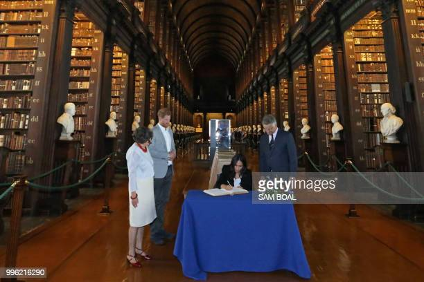 Meghan Duchess of Sussex signs the visitor's book during a visit with Britain's Prince Harry to Trinity College in Dublin on the final day of their...