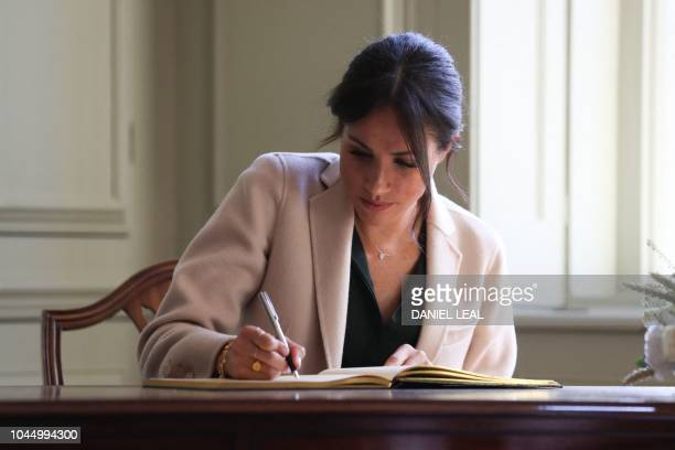 Meghan Duchess of Sussex signs the visitors book during an engagement at Edes House in Chichester West Sussex southern England on October 3 2018 The...