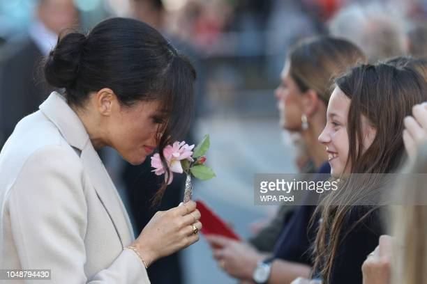 Meghan Duchess of Sussex smells a flower as she greets wellwishers as she arrives for an engagement at Edes House during an official visit to Sussex...