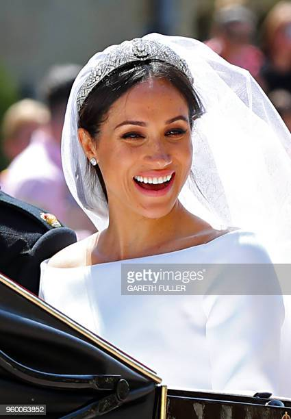 Meghan Duchess of Sussex smiles as she begins her carriage procession with Britain's Prince Harry Duke of Sussex in the Ascot Landau Carriage after...