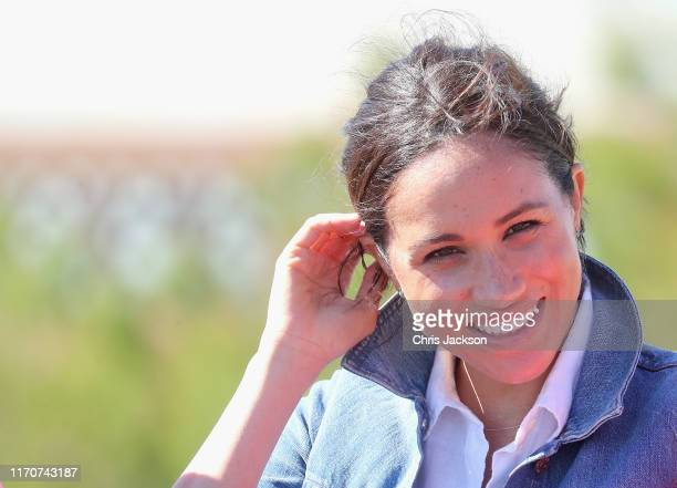 Meghan Duchess of Sussex smiles as she joins surf mentors and participates in a group activity to promote positive thinking with Prince Harry Duke of...