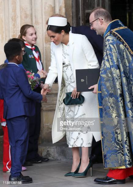 Meghan Duchess of Sussex speaks to a young wellwisher as she departs the Commonwealth Service on Commonwealth Day at Westminster Abbey on March 11...