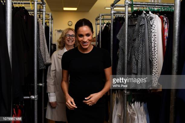 Meghan Duchess of Sussex walks through racks of clothes with Lady Juliet HughesHallett during her visit to Smart Works on January 10 2019 in London...