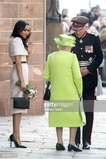 Meghan Duchess of Sussex waves as Queen Elizabeth II speaks with the Lord Lieutenant as they leave Chester Town Hall on June 14 2018 in Chester...
