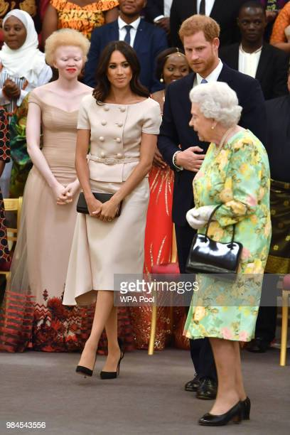 Meghan Duchess of Sussex with Queen Elizabeth II and Prince Harry Duke of Sussex at the Queen's Young Leaders Awards Ceremony at Buckingham Palace on...