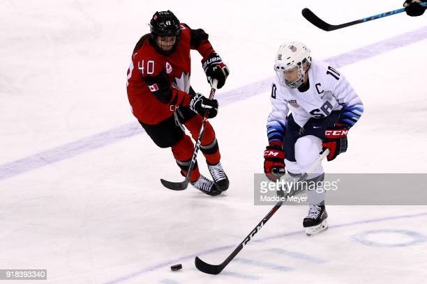 Meghan Duggan of the United States handles the puck against Blayre Turnbull of Canada during the Women's Ice Hockey Preliminary Round Group A game on...