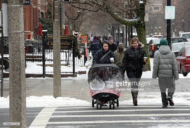 Meghan Joseph and Alexandra Corrigan push Henry and Sam along Newbury Street as a massive winter storm approaches the region with as much as two feet...