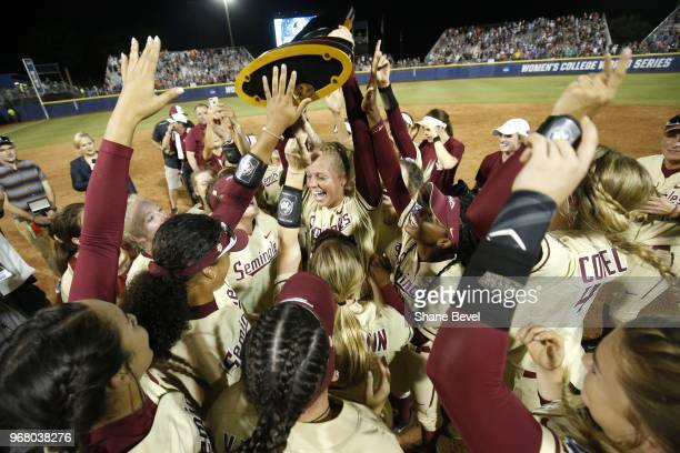 Meghan King of the Florida State Seminoles celebrates with the trophy after defeating the Washington Huskies during the Division I Women's Softball...