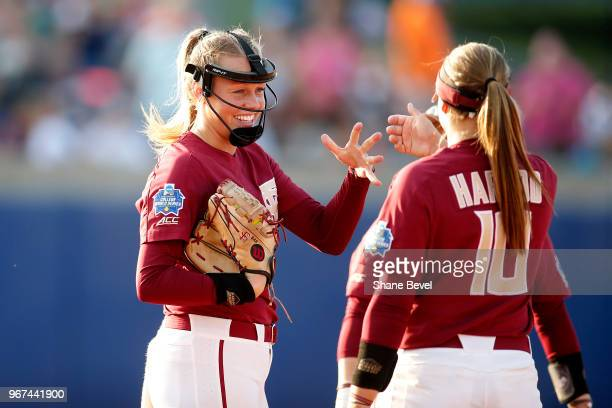 Meghan King of the Florida State Seminoles shares a moment with her teammates against the Washington Huskies during the Division I Women's Softball...