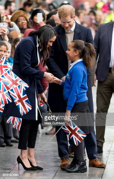 Meghan Markle hugs a child during a walkabout with Prince Harry at Millennium Point on March 8 2018 in Birmingham England