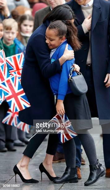 Meghan Markle hugs a young girl during a walkabout at Millennium Point before attending an event to celebrate International Women's Day on March 8...