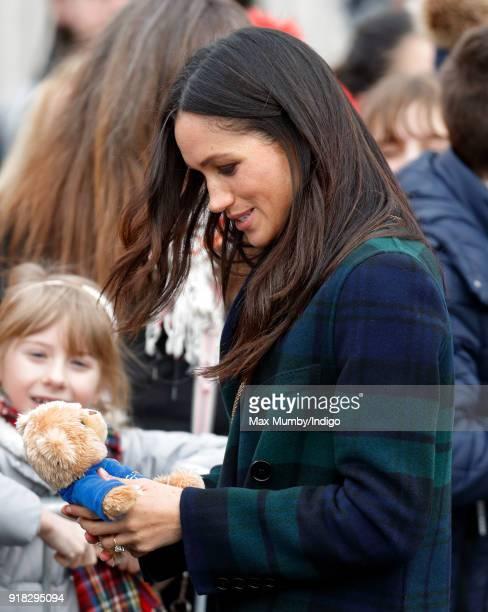 Meghan Markle receives a teddy bear from a member of the public as she visits Edinburgh Castle on February 13 2018 in Edinburgh Scotland