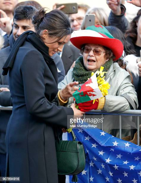 Meghan Markle receives a welsh flag and some daffodils from a member of the public during a walkabout as she visits Cardiff Castle on January 18 2018...