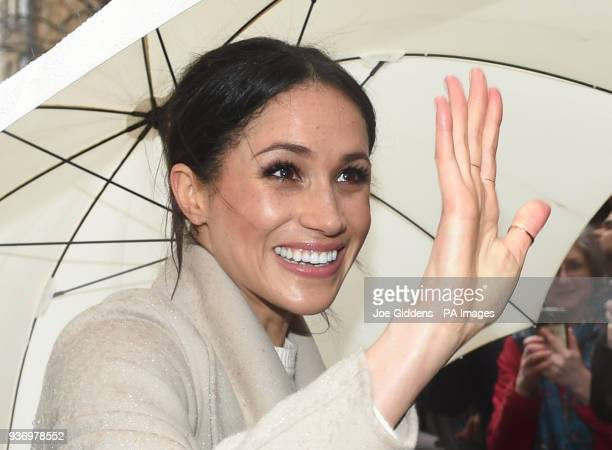 Meghan Markle shelters from the rain under an umbrella as she waves to wellwishers during a walkabout in Belfast after a visit to the Crown Bar in...
