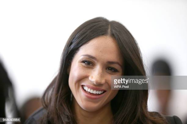 Meghan Markle smiles as she speaks with delegates from the Commonwealth Youth Forum at the Queen Elizabeth II Conference Centre during the...