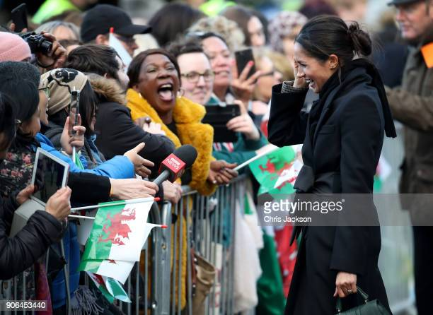 Meghan Markle talks to a member of the public as she arrives to a walkabout at Cardiff Castle on January 18 2018 in Cardiff Wales