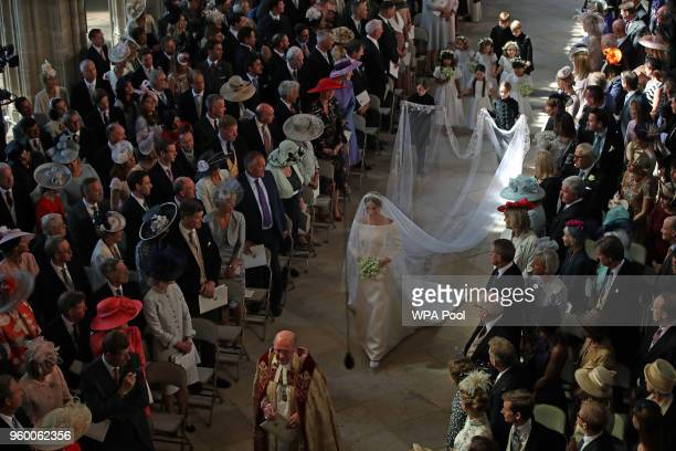 Meghan Markle walks down the aisle as she arrives at St George's Chapel at Windsor Castle for her wedding to Prince Harry on May 19 2018 in Windsor...