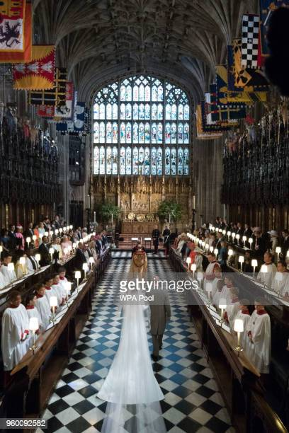 Meghan Markle walks up the aisle with the Prince Charles Prince of Wales at St George's Chapel at Windsor Castle during her wedding to Prince Harry...