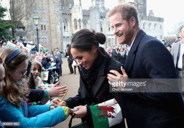 Meghan Markle writes a note for 10 year old Caitlin Clarke from Marlborough Primary School as Prince Harry looks on during a walkabout at Cardiff...