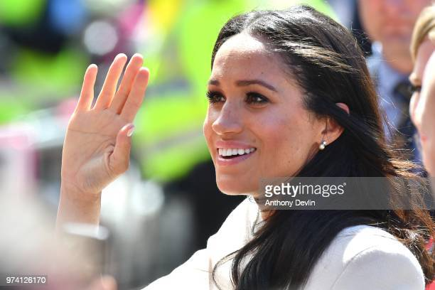Meghan The Duchess of Sussex waves as she joins Queen Elizabeth II to walk from Storyhouse to Chester Town Hall on June 14 2018 in Chester England...