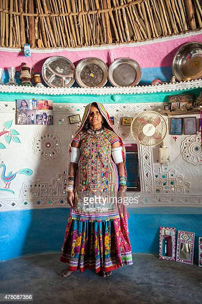 Meghawal tribal woman standing inside of her family's ornately painted mud brick hut in Hodka a semiarid region bordering the Great Raan of Kutch The...