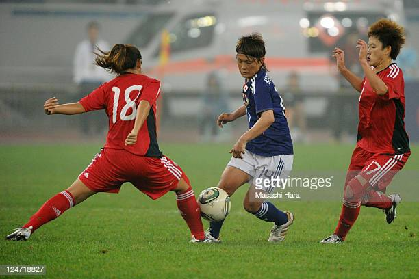 Megumi Kamionobe of Japan and Qu Shanshan Pang Fengyue of China compete for the ball during the London Olympic Women's Football Asian Qualifier match...