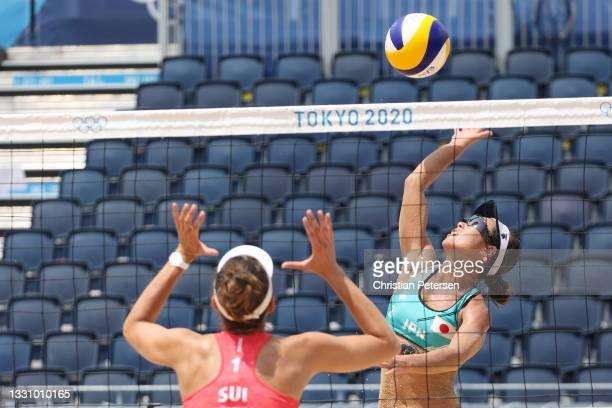 Megumi Murakami of Team Japan attacks against Tanja Huberli of Team Switzerland during the Women's Preliminary Round - Pool F beach volleyball on day...