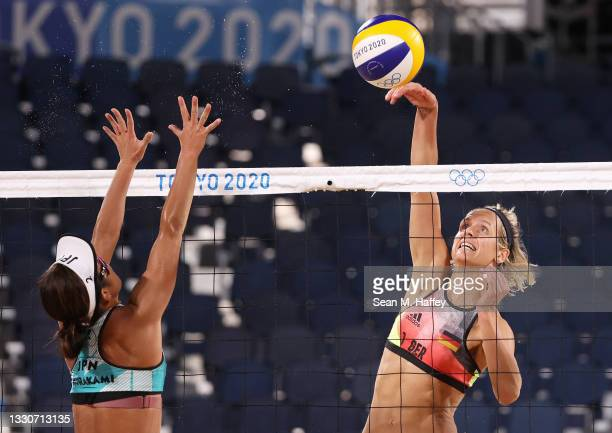 Megumi Murakami of Team Japan tries to block a shot from Laura Ludwig of Team Germany during the Women's Preliminary - Pool F beach volleyball on day...