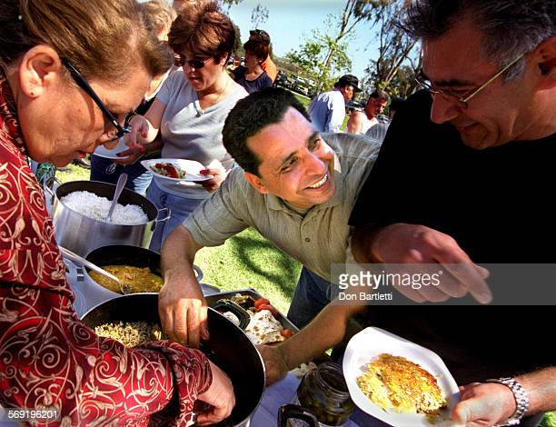 IRVINE –– Mehdi Ansari of Irvine banters with family and friends as he serves up a traditional Iranian meal of spicy barbequed chicken rice and...