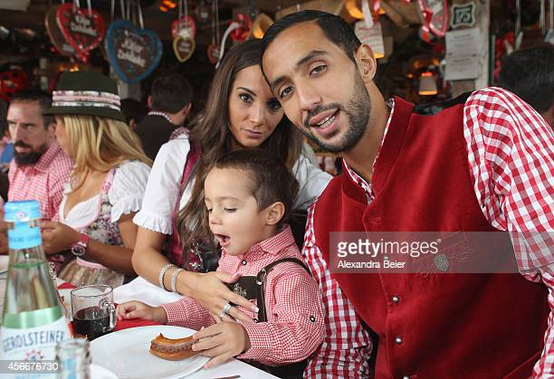 Mehdi Benatia of FC Bayern Muenchen his wife Cecile and son Kays attend the Oktoberfest 2014 beer festival at Kaefers Wiesenschaenke at...