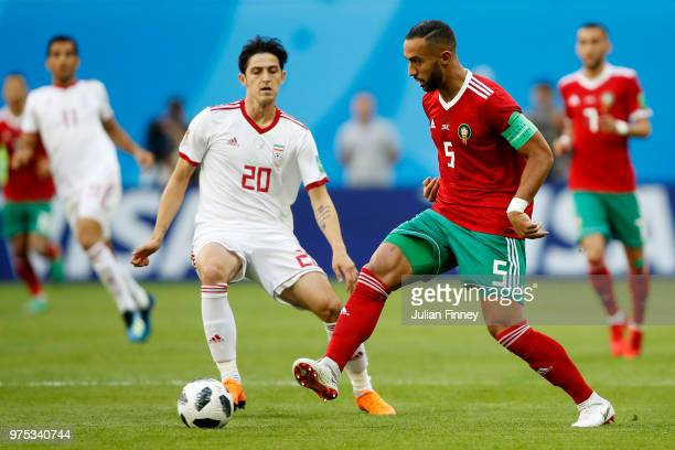 Mehdi Benatia of Morocco battles for possession with Sardar Azmoun of Iran during the 2018 FIFA World Cup Russia group B match between Morocco and...
