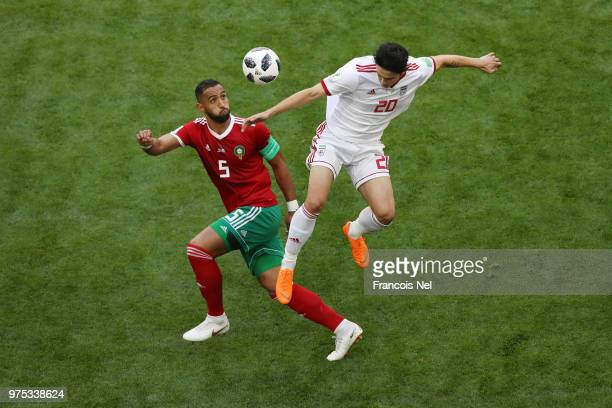 Mehdi Benatia of Morocco challenge for the ball with Sardar Azmoun of Iran during the 2018 FIFA World Cup Russia group B match between Morocco and...