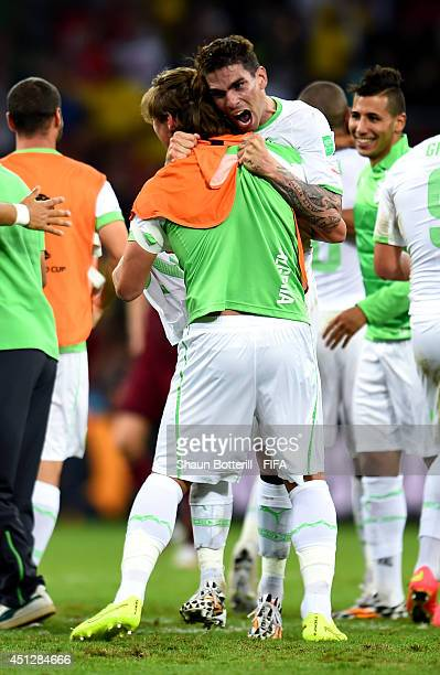 Mehdi Mostefa hugs Carl Medjani of Algeria after a 11 draw during the 2014 FIFA World Cup Brazil Group H match between Algeria and Russia at Arena da...