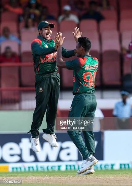 Mehidy Hasan Miraz and Mustafizur Rahman of Bangladesh celebrates the dismissal of Rovman Powell of West Indies during the 1st ODI match between West...