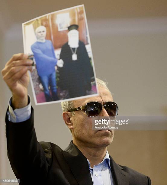 Mehmet Ali Agca who tried to assassinate John Paul II in 1981 displays an image showing him with Pope John Paul II during a press conference on...
