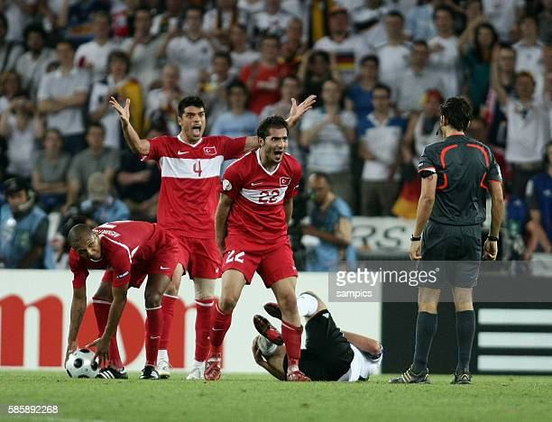 Mehmet Aurelio, Guekhan Zan, Hamit Altintop arguing with referee Massimo Busacca during the UEFA EURO 2008 Semifinals match between Germany and...