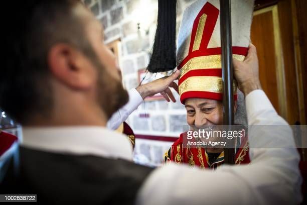 Mehmet Isik helps 65yearold Sadiye Inanc to wear her hat during a training of the female Mehter team in Turkish capital Ankara Turkey on July 20 2018...