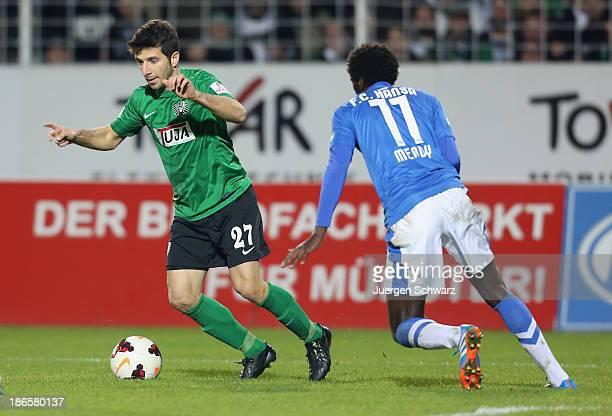 Mehmet Kara of Muenster controls the ball near Alexandre Mendy of Rostock during the Third League match between Preussen Muenster and Hansa Rostock...