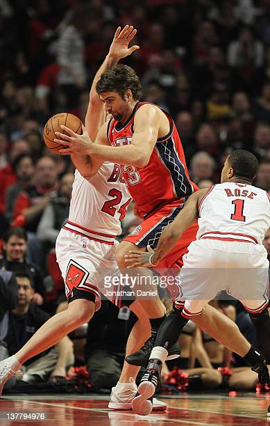 Mehmet Okur of the New Jersey Nets drives drives between Brian Scalabrine and Derrick Rose of the Chicago Bulls at the United Center on January 23...