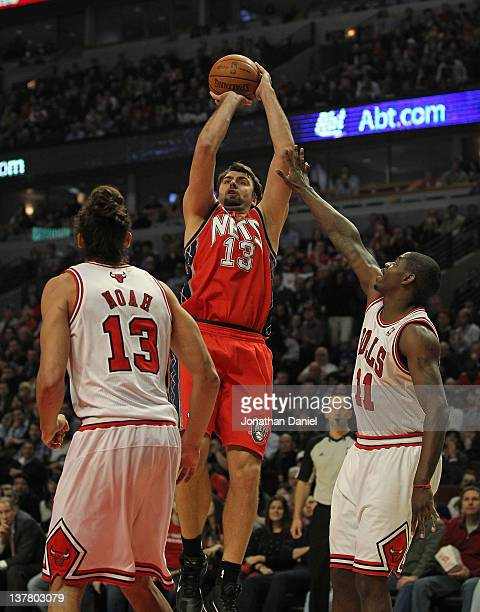 Mehmet Okur of the New Jersey Nets puts up a shot between Joakim Noah and Ronnie Brewer of the Chicago Bulls at the United Center on January 23 2012...
