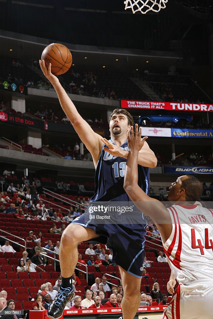Mehmet Okur #13 of the Utah Jazz shoots the ball over Chuck Hayes #44 of the Houston Rockets on April 7, 2010 at the Toyota Center in Houston, Texas.