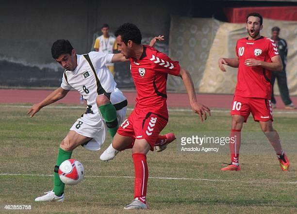 Mehmood Khan of Pakistan and Fardin of Afganistan struggle for ball during International friendly match at Punjab football stadium in Lahore Pakistan...