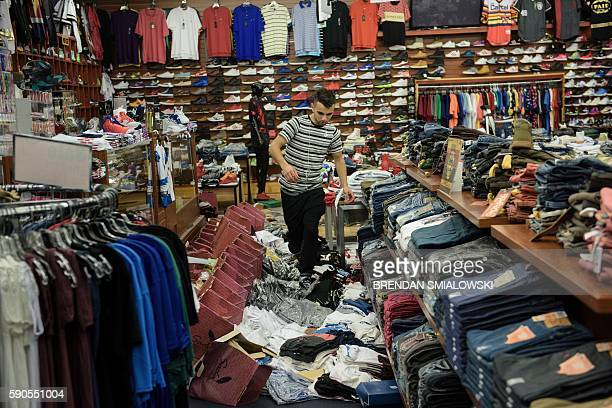 Mehmoud Elodeh walks over damaged merchandise as he checks on a clothing and shoe store following the floods on August 16, 2016 in Baton Rouge,...