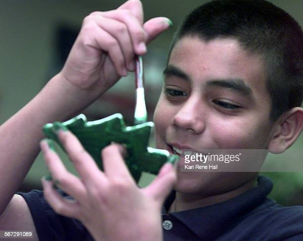 MEHolidaytreeD112498KRH––Robert Torres paints a Christmas tree ornament made of plastic molding dough during a resource specialist class for special...