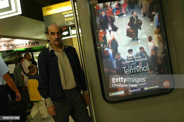 Mehran Karimi Nasseri who prefers to be known as Sir Alfred stands in front of a poster of Steven Spielberg's movie The Terminal loosely based on his...