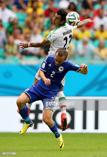 Mehrdad Pooladi of Iran and Avdija Vrsajevic of Bosnia and Herzegovina compete for the ball during the 2014 FIFA World Cup Brazil Group F match...