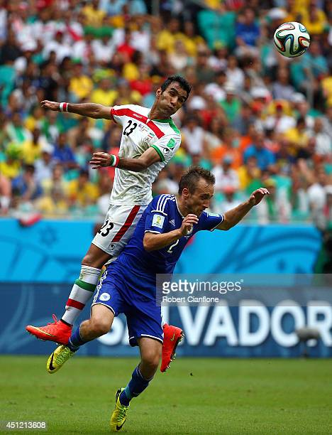 Mehrdad Pooladi of Iran and Avdija Vrsajevic of Bosnia and Herzegovina go up for a header during the 2014 FIFA World Cup Brazil Group F match between...